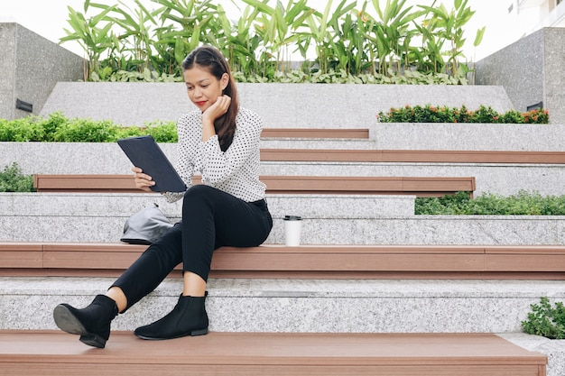 Positiva giovane imprenditrice multietnica seduta sui gradini all'aperto durante la pausa, bere caffè e leggere il romanzo sulla tavoletta digitale