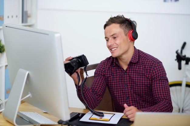 Giovane fotografo positivo che controlla le foto sulla fotocamera digitale che ha fatto caricare sul sito web