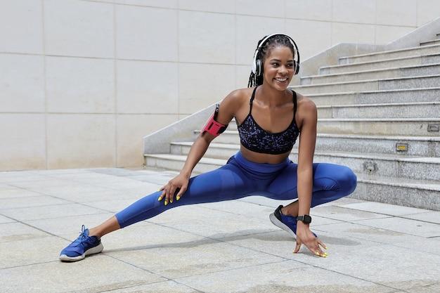 Positiva giovane donna con gli auricolari seguendo le indicazioni del suo allenatore tramite l'applicazione mobile quando fa esercizi di stretching all'aperto