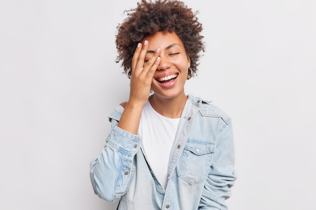 La giovane donna positiva fa il palmo del viso esprime emozioni autentiche sorride ampiamente vestita con abiti eleganti isolati su un muro bianco