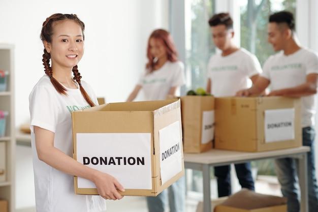 Giovane donna positiva in piedi in una scatola di cartone di donazione nell'ufficio della fondazione di beneficenza