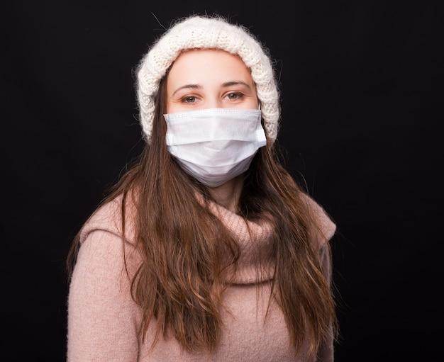Positiva la giovane donna che indossa la maschera medica, guardando a destra la telecamera.