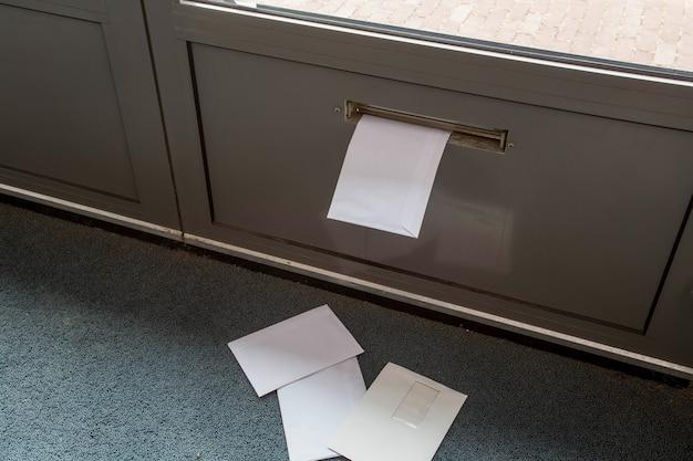 Post sdraiato sul pavimento e nella cassetta della posta della porta in un primo piano di un edificio vuoto