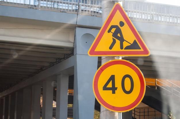 Posta con segnali stradali di avvertimento temporanei gialli: lavori di costruzione di strade e limite di velocità di 40 km / h, situato sullo sfondo di un ponte sfocato prima della riparazione della strada