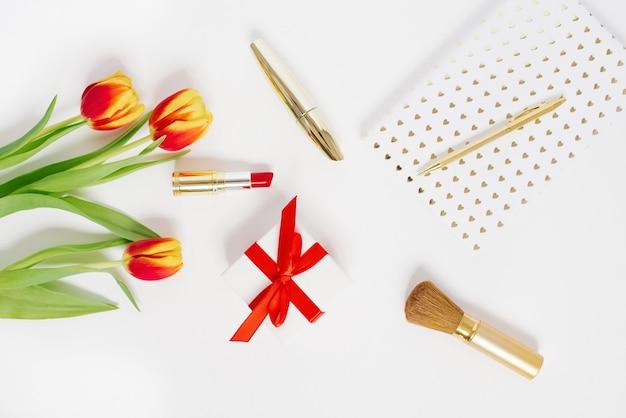 Cartolina per san valentino, festa della mamma o 8 marzo. un bouquet di tulipani, un regalo con un fiocco rosso, cosmetici e un taccuino con una penna. falt lay blogger