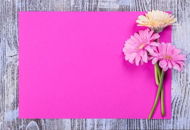 Cartolina con foglio di carta vuoto e fiori, superficie floreale per i saluti delle vacanze