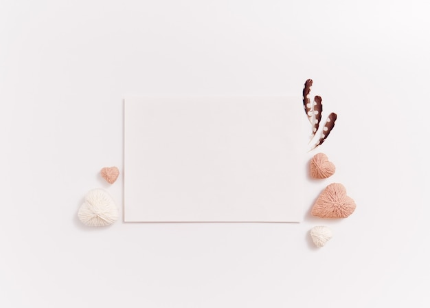 Cartolina con cuori artigianali fatti a mano e piuma su sfondo bianco