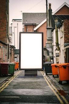 Tabellone per le affissioni del manifesto sulla priorità bassa sporca del vicolo della città. mockup del tabellone per le affissioni di pubblicità in bianco nella via