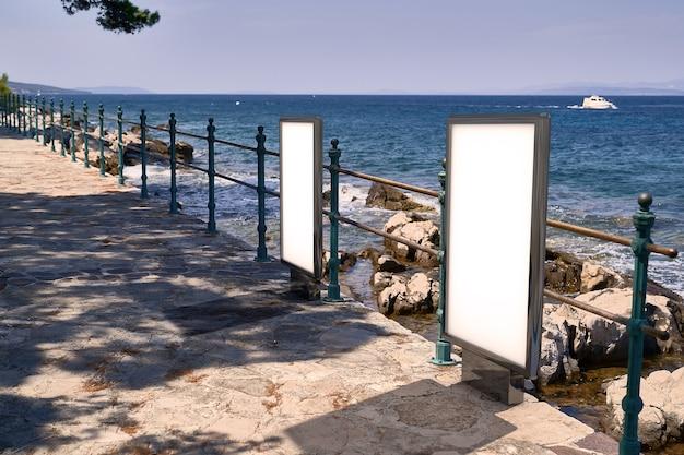 Tabellone per le affissioni di poster sulla costa del mare. mockup di cartelloni pubblicitari in bianco in strada