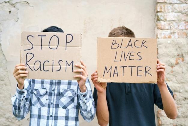 Poster che dice che la vita nera è importante e ferma il razzismo nelle mani di un giovane uomo