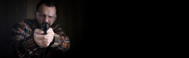 Poster con spazio vuoto per il testo su sfondo con uomo barbuto con occhiali protettivi e addestramento all'orecchio nel tiro con la pistola
