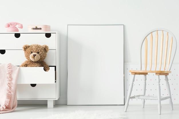 Poster con mockup tra sedia e armadietto con orsacchiotto all'interno della stanza dei bambini. foto reale. incolla qui il tuo poster