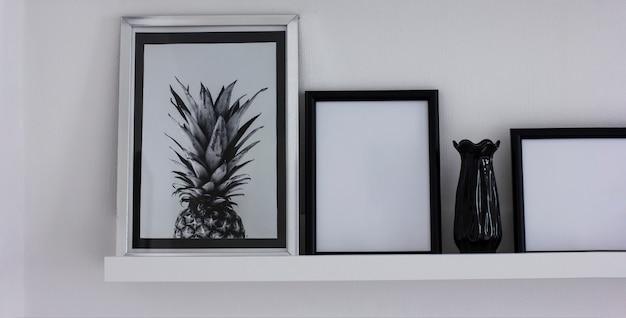 Manifesti con ananas e cornici pulite sullo scaffale, interni moderni in bianco e nero, banner