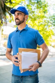 Postino che trasporta pacchi e lettere.