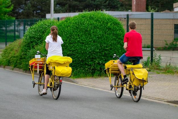Postino in sella alla sua bici da carico che effettua la posta nel quartiere.