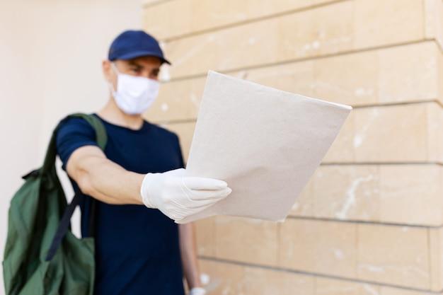 Postino in uniforme con guanti in lattice e sicurezza con maschera medica che consegna lettere alla cassetta postale di un destinatario durante la quarantena pandemica covid-19