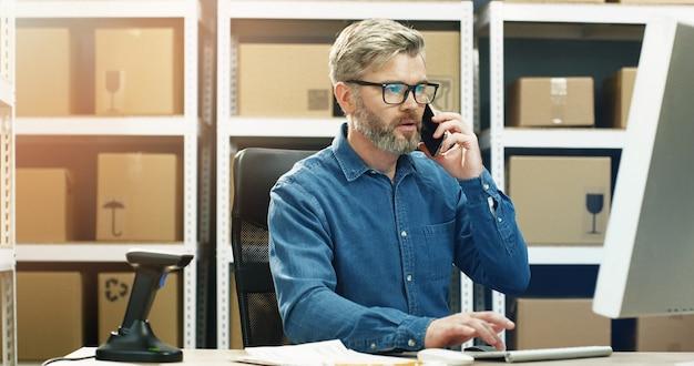 Postino che lavora al computer nell'ufficio postale di consegna e digitando sulla tastiera. mailman parlando su smartphone.