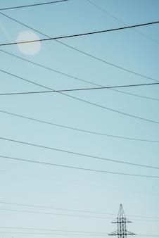 Poste con fili di alta tensione su sfondo di cielo blu al sole. immagine di sfondo di molti cavi in cielo con lo spazio della copia. gruppo di linee elettriche.