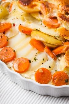 Gratin di patate e carote alle erbe in ciotola