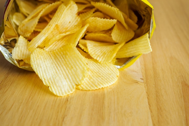 Sacchetto aperto di patatine fritte sulla tavola di legno