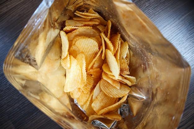 Patatine fritte in un sacchetto di snack aperto da vicino sul pavimento del tavolo