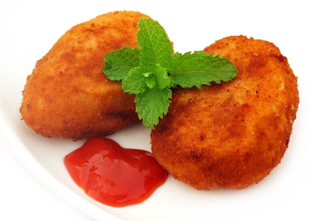 Costolette di patate con ketchup e foglie di menta fresca