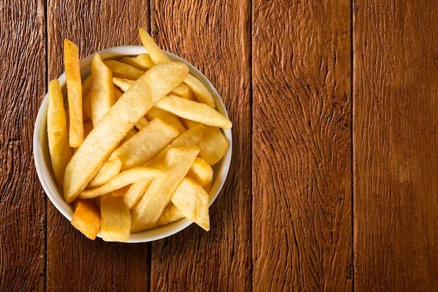 Porzione di patate fritte sullo sfondo di legno