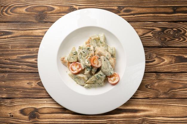 Gnocchi di patate con salsa blu dor e pomodorini in un piatto di ceramica bianca