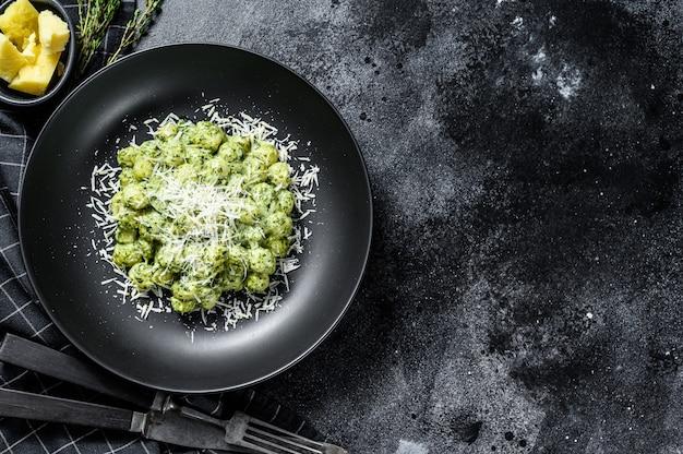 Gnocchi di patate con pesto, parmigiano e spinaci. pasta italiana. sfondo nero. vista dall'alto. copia spazio