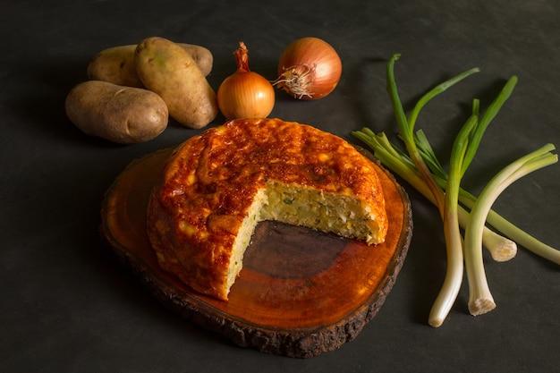 Frittata di patate con una porzione tagliata su una tavola di legno accanto a patate e cipolle su sfondo nero