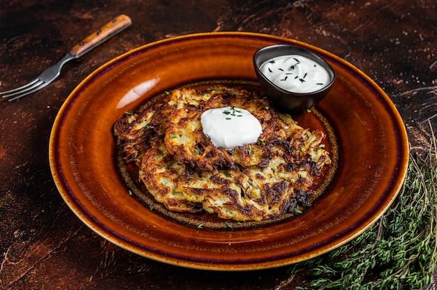Frittelle di patate o frittelle con salsa di panna in un piatto rustico. vista dall'alto.