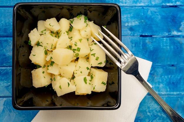 Insalata di patate e prezzemolo in una ciotola nera su una superficie blu rustica. cibo sano e naturale.