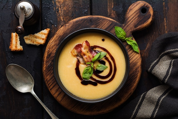 Crema di zuppa di patate con pancetta e salsa di soia in ciotola nera, sulla vecchia superficie di cemento scuro