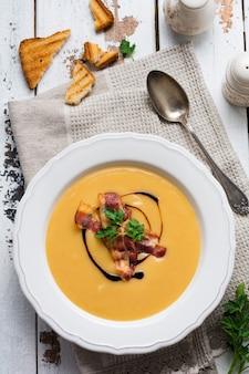 Crema di zuppa di patate con pancetta e salsa di soia in una ciotola bianca, sulla superficie in legno vecchio chiaro