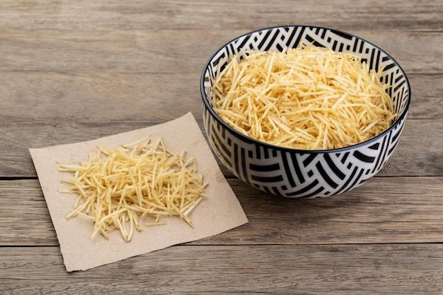 Paglia di patate o patata ridotta in una ciotola su un tavolo di legno.