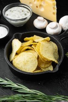 Patatine fritte con formaggio e cipolla, su sfondo di pietra nera