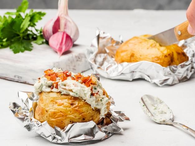 Sul tavolo giacciono le patate al cartoccio con ripieno di crema di formaggio.