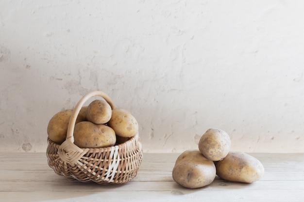 Merce nel carrello delle patate sulla vecchia parete bianca
