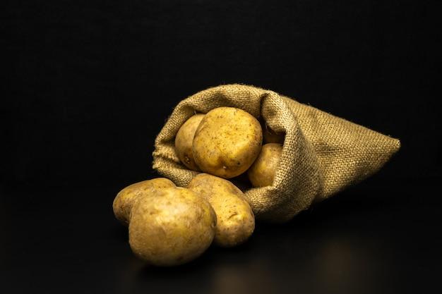 Patate su uno sfondo nero, sacchetto di patate