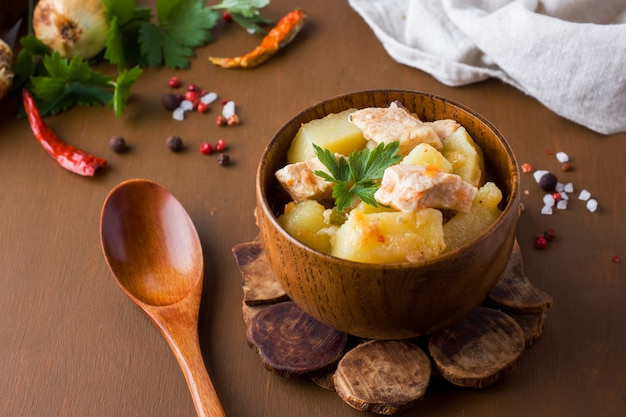 Patate in umido con pollo e verdure in una ciotola di legno.