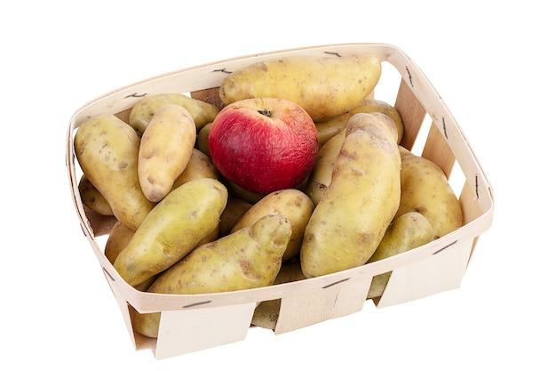 Patate in un vassoio con una mela in modo che non germogli su una superficie bianca
