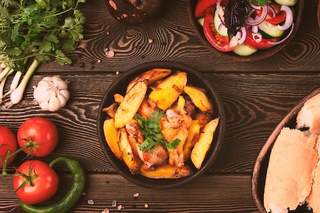 Patate con pollo fritto piatto su una padella di argilla ketsi ojakhuri cucina georgiana stile rustico