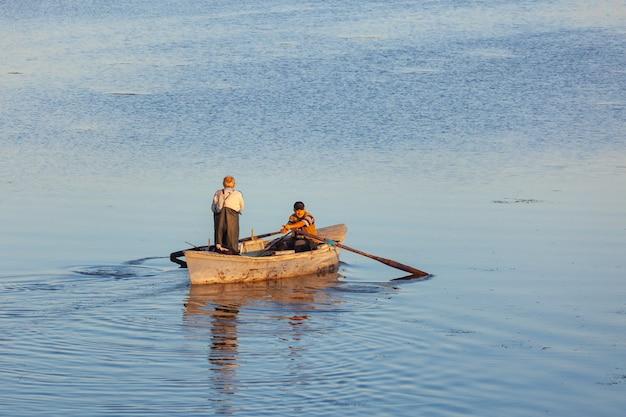 Poti, georgia - 01.09.2019: una piccola barca e i pescatori sul lago a paliastomi. poti. natura.