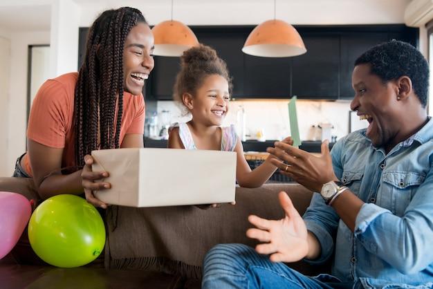 Potrait di un padre sorpreso di ricevere un regalo dalla moglie e dalla figlia mentre era a casa.