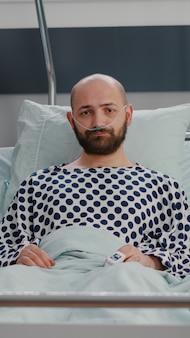 Potrait di un uomo malato triste che indossa un tubo nasale dell'ossigeno che giace in cattive condizioni guardando la telecamera durante il recupero della malattia in ospedale
