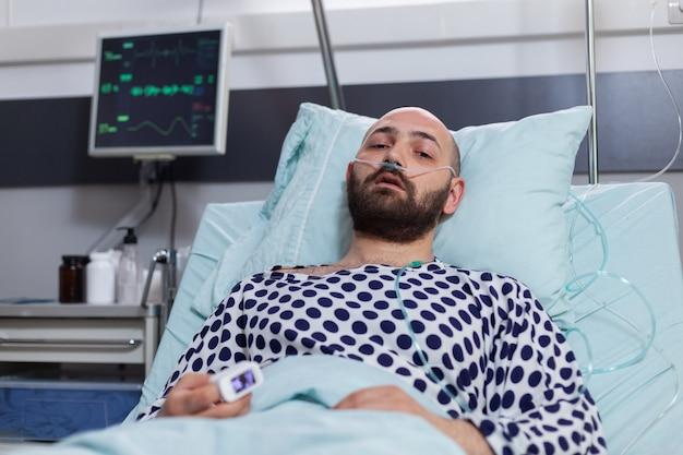 Potrait di un uomo malato che indossa un tubo dell'ossigeno nasale con una malattia respiratoria sdraiato a letto durante il recupero...