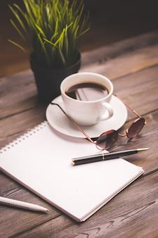 Taccuini con fiori in vaso, penne, cancelleria e bicchieri da caffè, tavolo in legno
