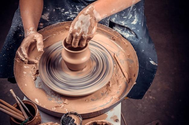 La studentessa potter crea una nuova ceramica dall'argilla su un tornio da vasaio. fatto a mano. avvicinamento.