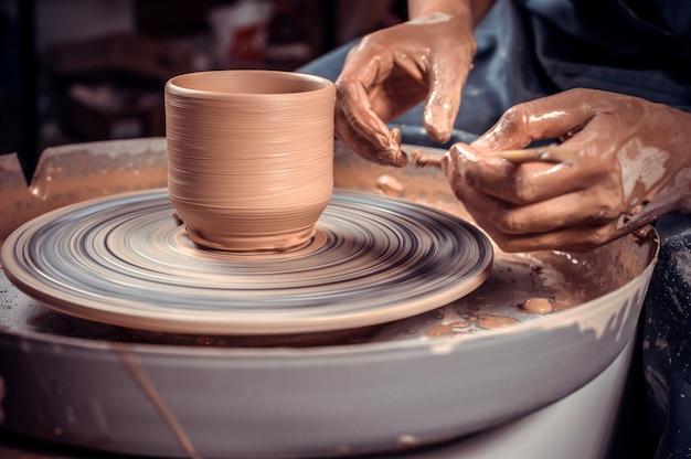 Potter studentessa che fa ceramiche, scultore da argilla bagnata su ruota