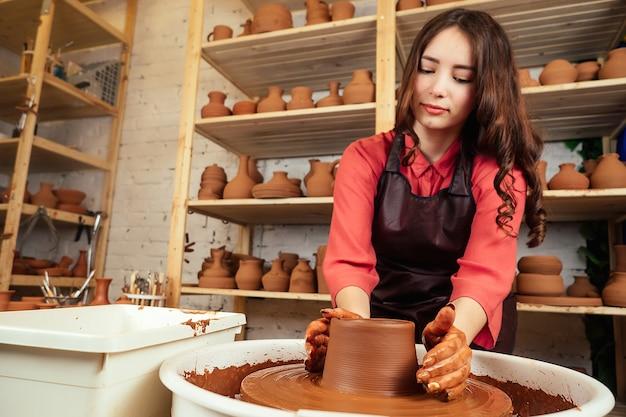 Il vasaio modella una pentola di mastrelli da un'argilla. una donna lavora con l'argilla su un tornio da vasaio. il concetto di arte e meditazione con la modellazione dell'argilla